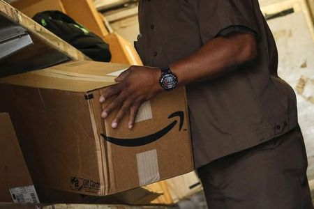 Worker carries an Amazon box to be delivered in New York