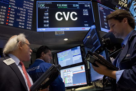 Traders gather at the post that trades Cablevision on the floor of the New York Stock Exchange