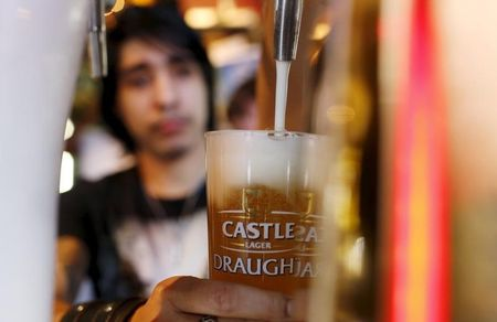 A barman pours a beer produced by brewing company SAB Miller at a bar in Cape Town