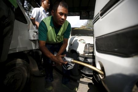 A worker fills petrol on a vehicle at the petrol pump in in Kathmandu