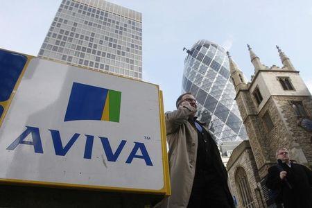 Pedestrians walk past an Aviva logo outside the company's head office in the city of London