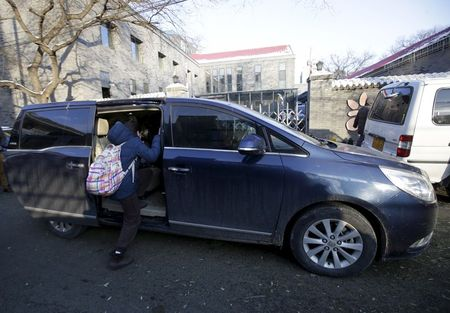 A primary school student gets into a minivan as her mother picks her up outside her school, in Beijing