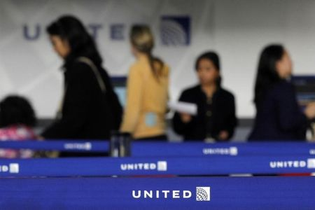 Customers of United wait in line to check in at Newark International airport in New Jersey
