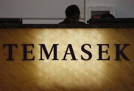 Receptionist stands behind a logo of state investor Temasek Holdings at their office in Singapore