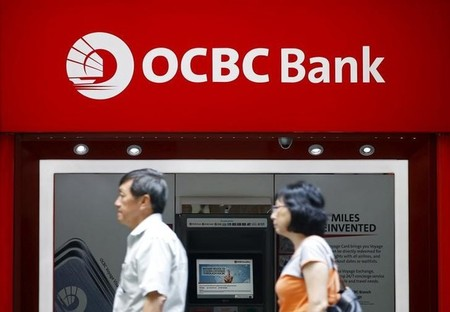 People pass an Oversea-Chinese Banking Corporation (OCBC) bank automated teller machine in Singapore's central business district in Singapore's central business district
