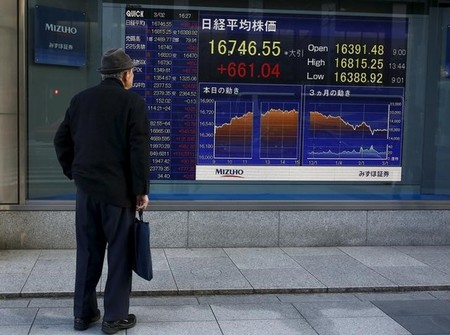 A man looks at an electronic board displaying the Nikkei average outside a brokerage in Tokyo