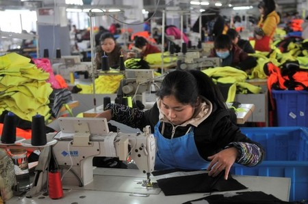 Employee works at a garment factory, which exports products to Europe, in Hefei, Anhui province