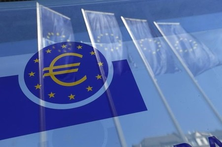 European Union flags are reflected in a window at the headquarters of ECB in Frankfurt