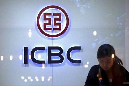 A teller at a branch of the Industrial and Commercial Bank of China (ICBC) works behind the counter in central Sydney, Australia