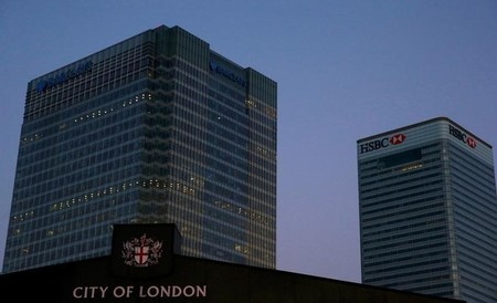 Office lights are on in banks as dawn breaks behind the financial district of Canary Wharf, in London