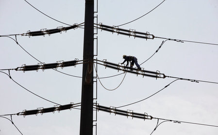 An employee of K-Electric fixes cables on a power transmission tower in Karachi,