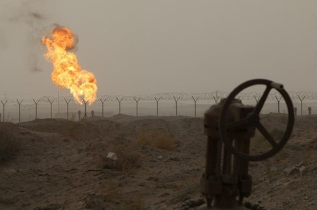 Flames emerge from a pipeline at the oil fields in Basra, southeast of Baghdad