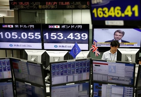 An employees of a foreign exchange trading company works next to monitors displaying television news on Britain's EU referendum, Japan's Nikkei share average, the Japanese yen's exchange rate against British pound and the U.S. dollar in Tokyo, Japan