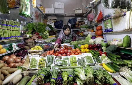 A vendor reaches out for vegetables at her shop in a market in Beijing