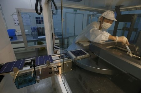 An employee works on a production line of solar panel at a factory of a photovoltaic company in Jiaxing