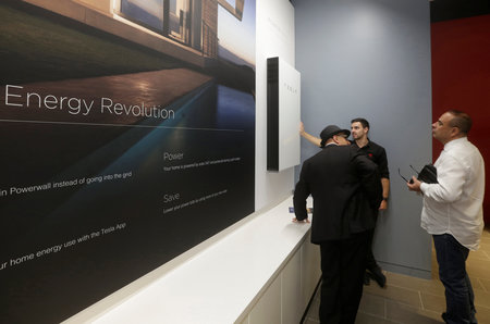 A Tesla representative demonstrates the Tesla Powerwall battery storage device to potential customers at the Tesla store in Sydney, Australia