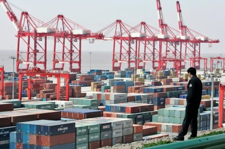 FILE PHOTO: A man watches containers at the Yangshan deepwater port in Shanghai