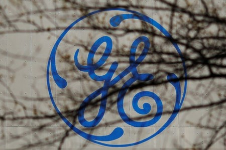 The logo of a General Electric facility is seen behind tree branches in Medford