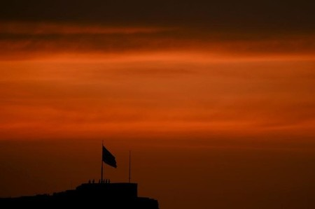 Greek soldiers are silhouetted during a ceremony to bring down the national flag atop the Acropolis hill during sunset in Athens
