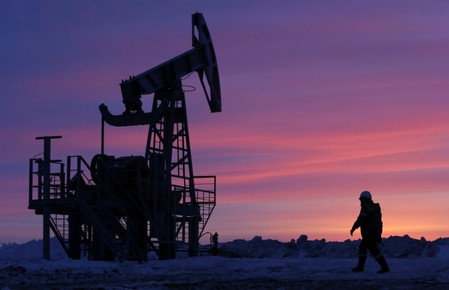 FILE PHOTO: A worker walks past a pump jack on an oil field owned by the Bashneft company near Nikolo-Berezovka
