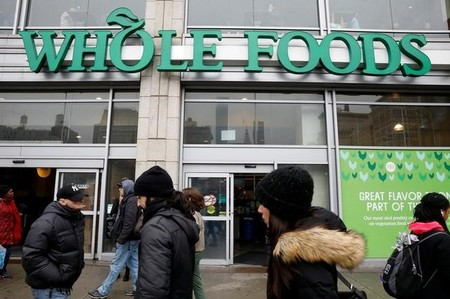 People pass by a Whole Foods Market in New York