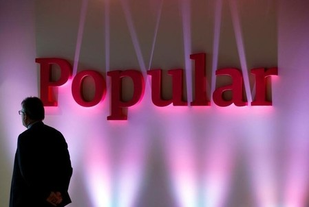 FILE PHOTO: A man stands next to the logo of Spain's Banco Popular during the bank's results presentation in Madrid