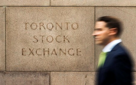 FILE PHOTO - A man walks past an old Toronto Stock Exchange sign in Toronto