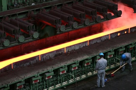 Chinese employees work near a machine for hot-rolled steel at the Baosteel factory in Shanghai.