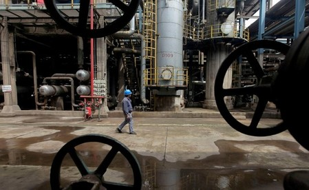 FILE PHOTO: A worker walks past oil pipes at a refinery in Wuhan
