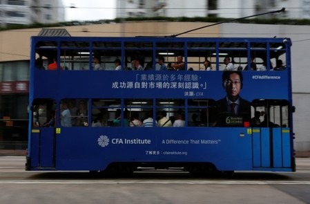 A tram with an advertisement of CFA Institute featuring Hao Hong drives past in Hong Kong