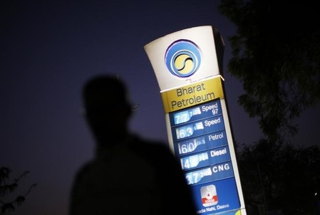 A Bharat Petroleum oil pump station displays the price of unleaded petrol and Diesel as a pedestrian walks past in New Delhi