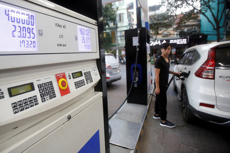 FILE PHOTO: A man pumps petrol for his car at a petrol station in Hanoi
