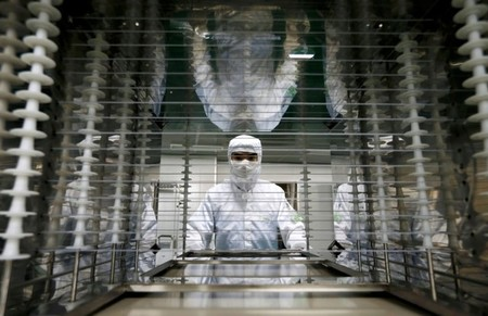FILE PHOTO: An employee works inside an electronic products factory in Huzhou