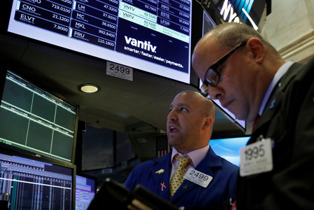 Traders work at the post where U.S. credit card technology firm Vantiv Inc is traded on the floor of the NYSE in New York