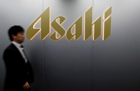 FILE PHOTO: Man walks past the logo of Asahi Group Holdings at the company's headquarters in Tokyo