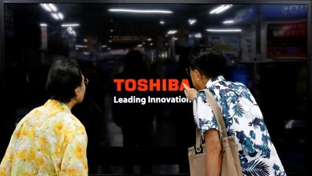 FILE PHOTO: Shoppers look at Toshiba Corp's Regza television at an electronics store in Yokohama