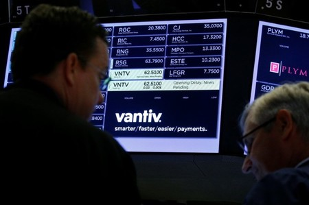 Traders wait for news at the post where U.S. credit card technology firm Vantiv Inc is traded on the floor of the NYSE in New York