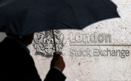 FILE PHOTO: A man shelters under an umbrella as he walks past the London Stock Exchange