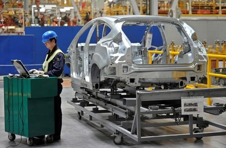 An employee uses a laptop next to a car body at an assembly line at a Ford manufacturing plant in Chongqing