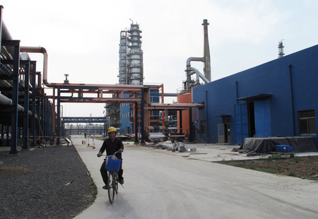 FILE PHOTO: An employee rides a bike on a road near refinery plants of Chambroad Petrochemicals, in Boxing