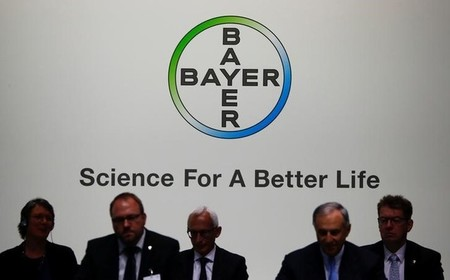 Members of the supervisory board of German pharmaceutical and chemical maker Bayer AG are silhouetted against the company's logo at the annual general shareholders meeting in Bonn
