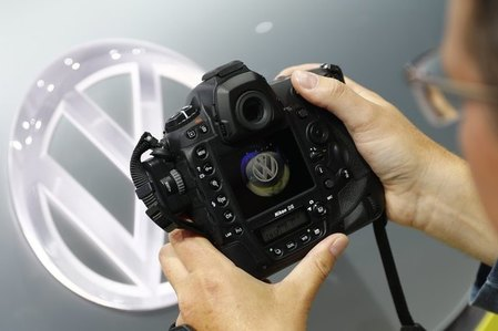 A photographer takes a picture of a Volkswagen logo before the opening of the Frankfurt Motor Show