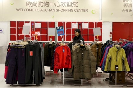 An employee waits for customers at Sun Art Retail Group's Auchan hypermarket store in Beijing