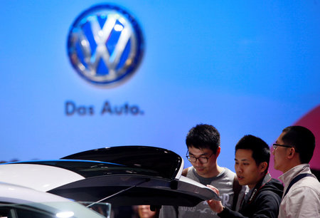 FILE PHOTO: Guests look at a Volkswagen car during the media day at 15th Shanghai International Automobile Industry Exhibition in Shanghai