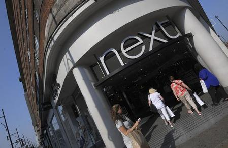 Shoppers pass a branch of Next retail in London, Britain
