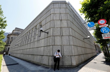 A man looks at a mobile phone in front of the Bank of Japan building in Tokyo