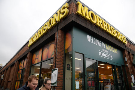FILE PHOTO: Shoppers walk past a branch of the food retailer Morrisons in west London, Britain
