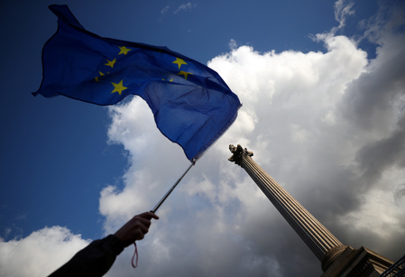 A demonstrator waves a European Union flag in front of Nelson's column in London