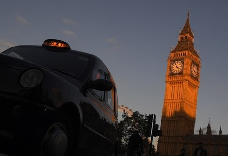 A London black cab taxi drives past Big Ben and the Houses of Parliament in late afternoon sunlight in London