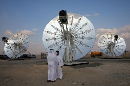 Men stand in front of solar panels at the Mohammed bin Rashid Al Maktoum Solar Park in Dubai